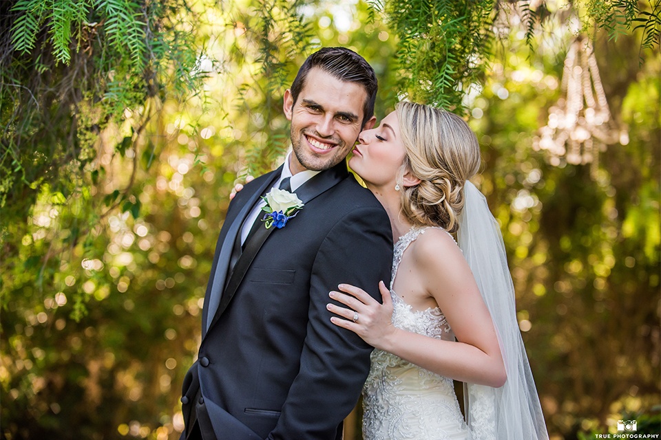 San diego wedding at green gables estate bride form fitting lace gown with a long train and high illusion neckline with long veil and groom black shawl lapel tuxedo with matching vest and white dress shirt with long black skinny tie and white floral boutonniere hugging
