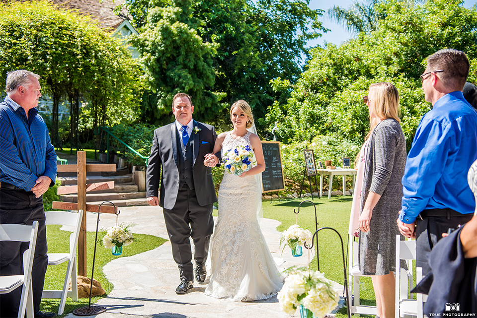 San diego wedding at green gables estate bride form fitting lace gown with a long train and high illusion neckline with long veil holding white and blue floral bridal bouquet walking down the aisle with dad