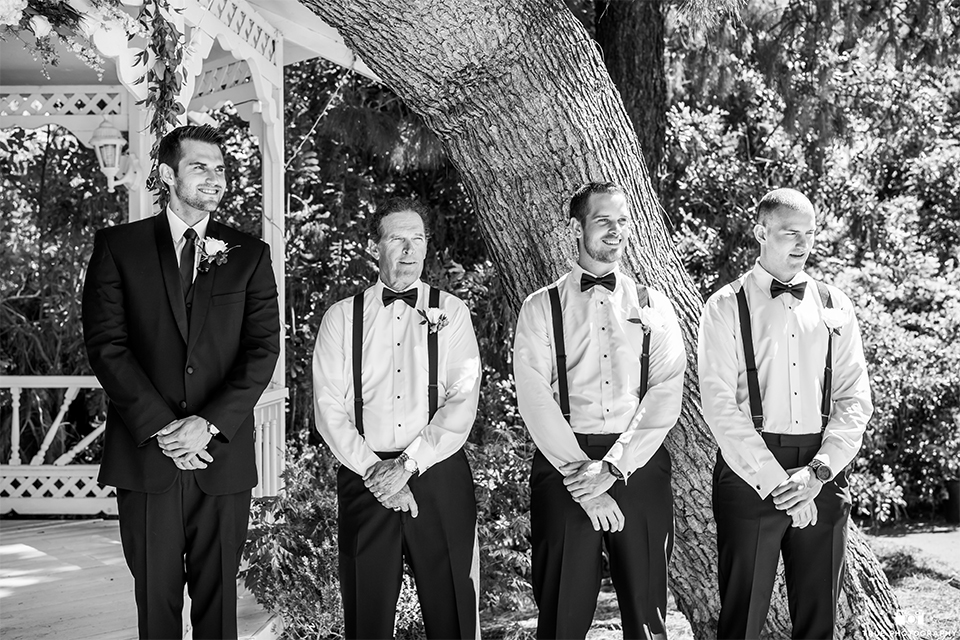 San diego wedding at green gables estate groom black shawl lapel tuxedo with matching vest and white dress shirt with long black skinny tie and white floral boutonniere with groomsmen bow ties and suspenders standing watching bride walk down the aisle during ceremony black and white photo