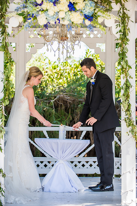 San diego wedding at green gables estate bride form fitting lace gown with a long train and high illusion neckline with long veil and groom black shawl lapel tuxedo with matching vest and white dress shirt with long black skinny tie and white floral boutonniere ceremony