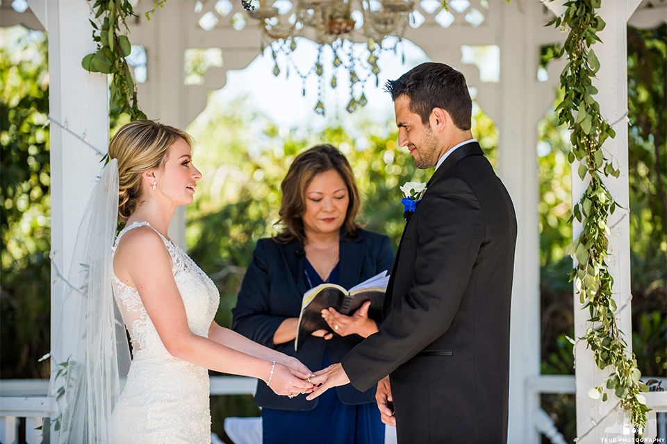 San diego wedding at green gables estate bride form fitting lace gown with a long train and high illusion neckline with long veil and groom black shawl lapel tuxedo with matching vest and white dress shirt with long black skinny tie and white floral boutonniere holding hands during ceremony