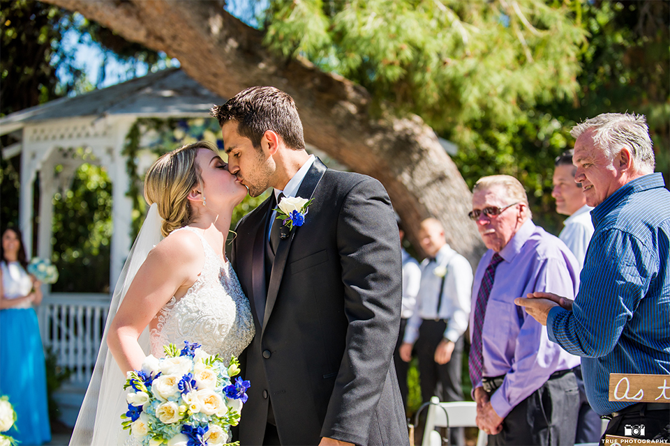 San diego wedding at green gables estate bride form fitting lace gown with a long train and high illusion neckline with long veil and groom black shawl lapel tuxedo with matching vest and white dress shirt with long black skinny tie and white floral boutonniere kissing after ceremony bride holding white and blue floral bridal bouquet