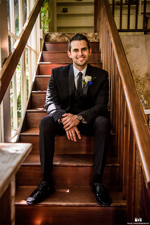 San diego wedding at green gables estate groom black shawl lapel tuxedo with matching vest and white dress shirt with long black skinny tie and white floral boutonniere sitting on stair case