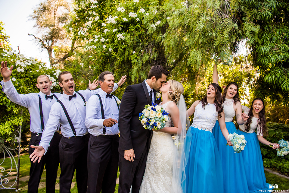 San diego wedding at green gables estate bride form fitting lace gown with a long train and high illusion neckline with long veil and groom black shawl lapel tuxedo with matching vest and white dress shirt with long black skinny tie and white floral boutonniere kissing holding white and blue floral bridal bouquet with wedding party bridesmaids white and blue dresses and groomsmen bow ties and suspenders