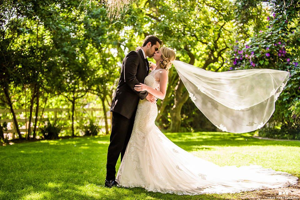 San diego wedding at green gables estate bride form fitting lace gown with a long train and high illusion neckline with long veil and groom black shawl lapel tuxedo with matching vest and white dress shirt with long black skinny tie and white floral boutonniere kissing