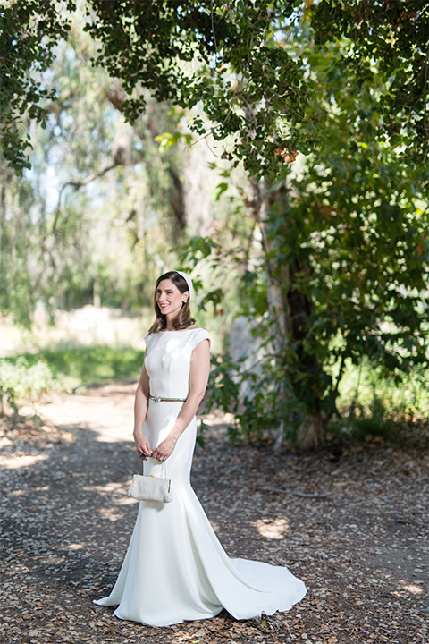Orange county outdoor wedding at the green parrot villa bride form fitting white gown with a high neckline and crystal belt with short veil
