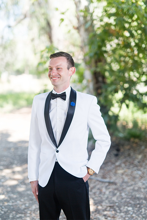 Orange county outdoor wedding at the green parrot villa groom white tuxedo jacket with black shawl lapel tuxedo and black pants with white dress shirt and black bow tie standing with hands in pockets