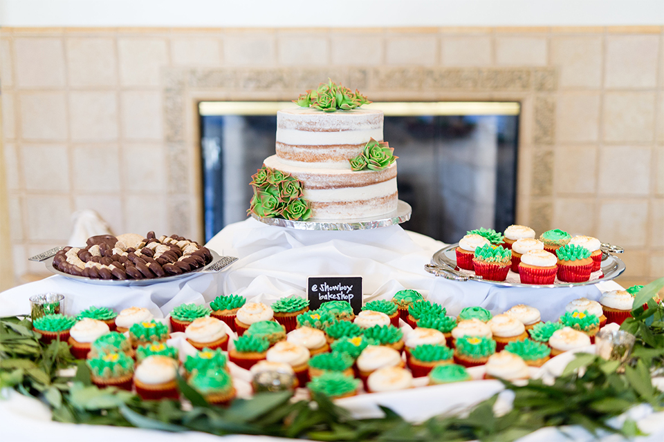 Orange county outdoor wedding shoot at the green parrot villa table set up white table linen with white place settings and wine glasses with greenery floral decor in center and black and white table numbers with two tier white naked wedding cake and green and white cupcakes on table