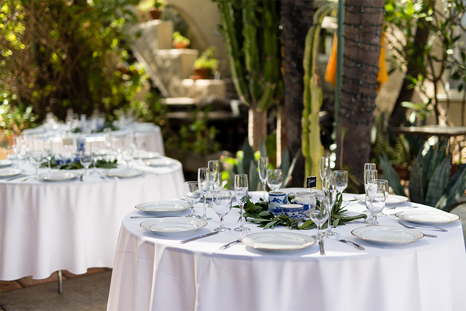Orange county outdoor wedding shoot at the green parrot villa table set up white table linen with white place settings and wine glasses with greenery floral decor in center and black and white table numbers