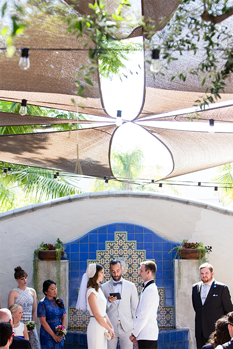 Orange county outdoor wedding at the green parrot villa bride form fitting white gown with a high neckline and crystal belt with short veil and groom white tuxedo jacket with black shawl lapel and black pants with white dress shirt and black bow tie holding hands during ceremony