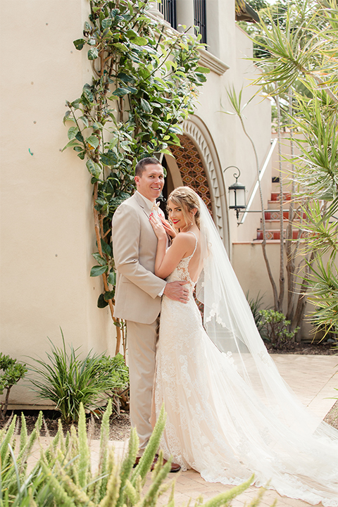 Los angeles wedding at los verdes golf club bride form fitting gown with lace detail and low back design with thin straps and long veil with groom tan notch lapel suit with matching vest and white dress shirt with matching tan bow tie and white pocket square with white and red floral boutonniere