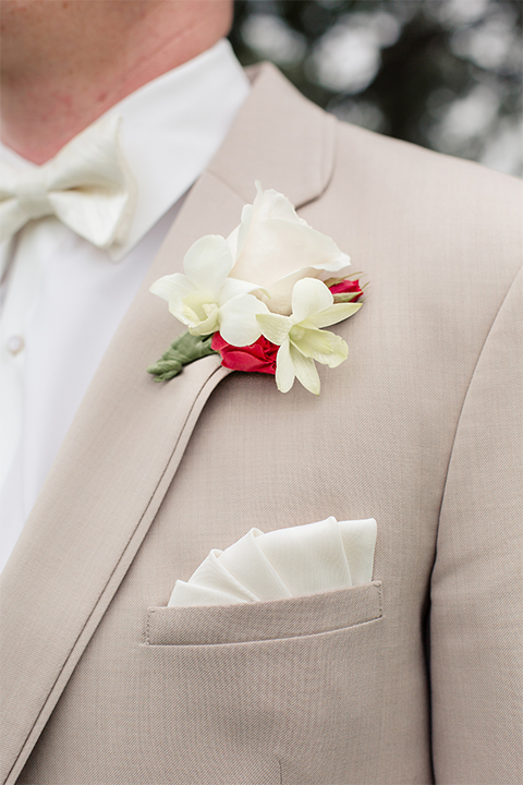 Los angeles wedding at los verdes golf club groom tan notch lapel suit with matching vest and white dress shirt with matching tan bow tie and white pocket square with white and red floral boutonniere close up