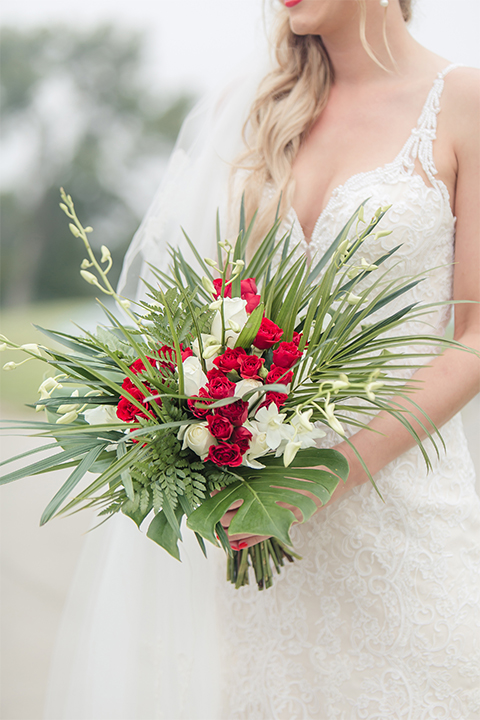 Los angeles wedding at los verdes golf club bride form fitting gown with lace detail and low back design with thin straps and long veil holding red and white floral bridal bouquet close up