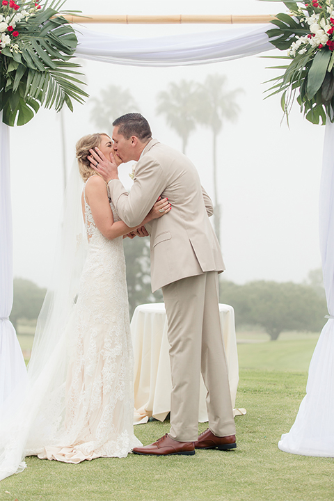 Los angeles wedding at los verdes golf club bride form fitting gown with lace detail and low back design with thin straps and long veil with groom tan notch lapel suit with matching vest and white dress shirt with matching tan bow tie and white pocket square with white and red floral boutonniere kissing during ceremony