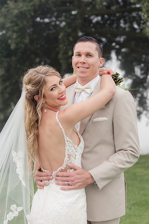 Los angeles wedding at los verdes golf club bride form fitting gown with lace detail and low back design with thin straps and long veil with groom tan notch lapel suit with matching vest and white dress shirt with matching tan bow tie and white pocket square with white and red floral boutonniere hugging