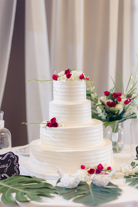 Los verdes golf club wedding table set up white table linens with dark chairs and white and green and red flower centerpiece decor with wine glasses and table numbers with wedding cake four tier white wedding cake with red and white flowers on white table linen