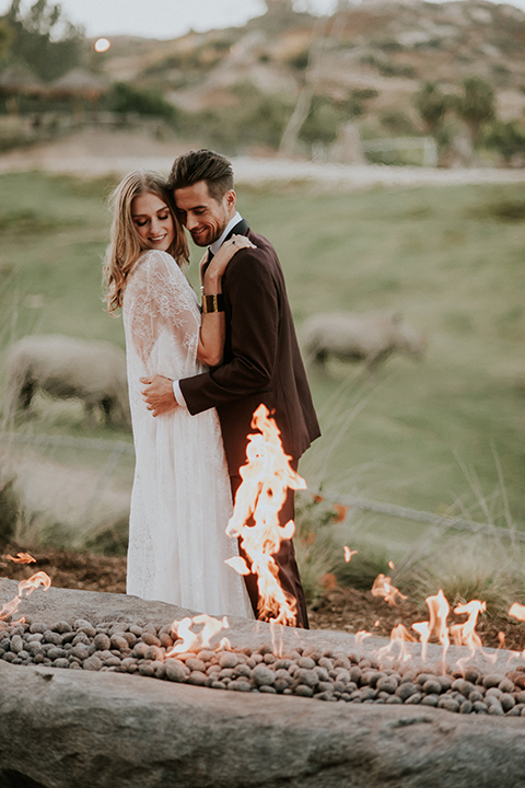 San diego outdoor wedding shoot at the san diego zoo and safari park bride white chiffon gown with lace sleeves and thin straps with plunging neckline and groom burgundy shawl lapel tuxedo with white dress shirt and long black skinny tie and black shoes standing and hugging by fire