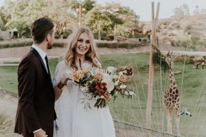 San diego outdoor wedding shoot at the san diego zoo and safari park bride white chiffon gown with lace sleeves and thin straps with plunging neckline and groom burgundy shawl lapel tuxedo with white dress shirt and long black skinny tie and black shoes standing and hugging with giraffe in background bride holding white and orange floral bridal bouquet
