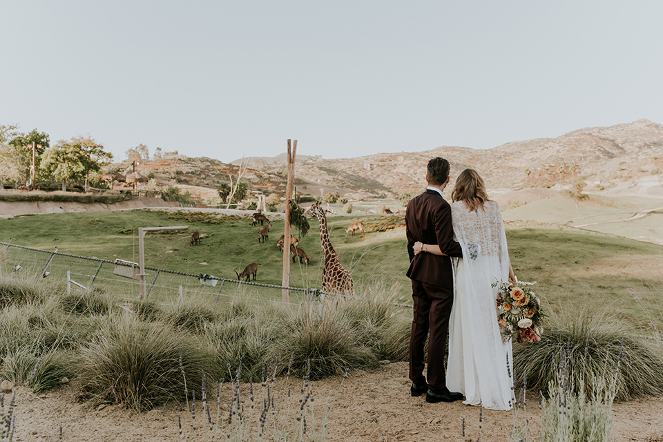 San diego outdoor wedding shoot at the san diego zoo and safari park bride white chiffon gown with lace sleeves and thin straps with plunging neckline and groom burgundy shawl lapel tuxedo with white dress shirt and long black skinny tie and black shoes standing and hugging watching giraffe bride holding white and orange floral bridal bouquet