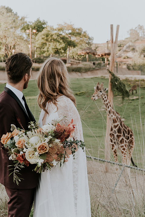 San diego outdoor wedding shoot at the san diego zoo and safari park bride white chiffon gown with lace sleeves and thin straps with plunging neckline and groom burgundy shawl lapel tuxedo with white dress shirt and long black skinny tie and black shoes hugging and bride holding white and orange floral bridal bouquet