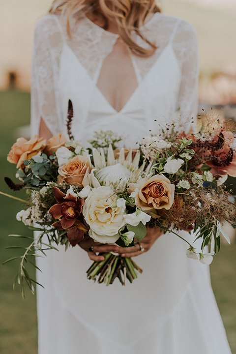 San diego outdoor wedding shoot at the san diego zoo and safari park bride white chiffon gown with lace sleeves and thin straps with plunging neckline holding white and orange floral bridal bouquet close up