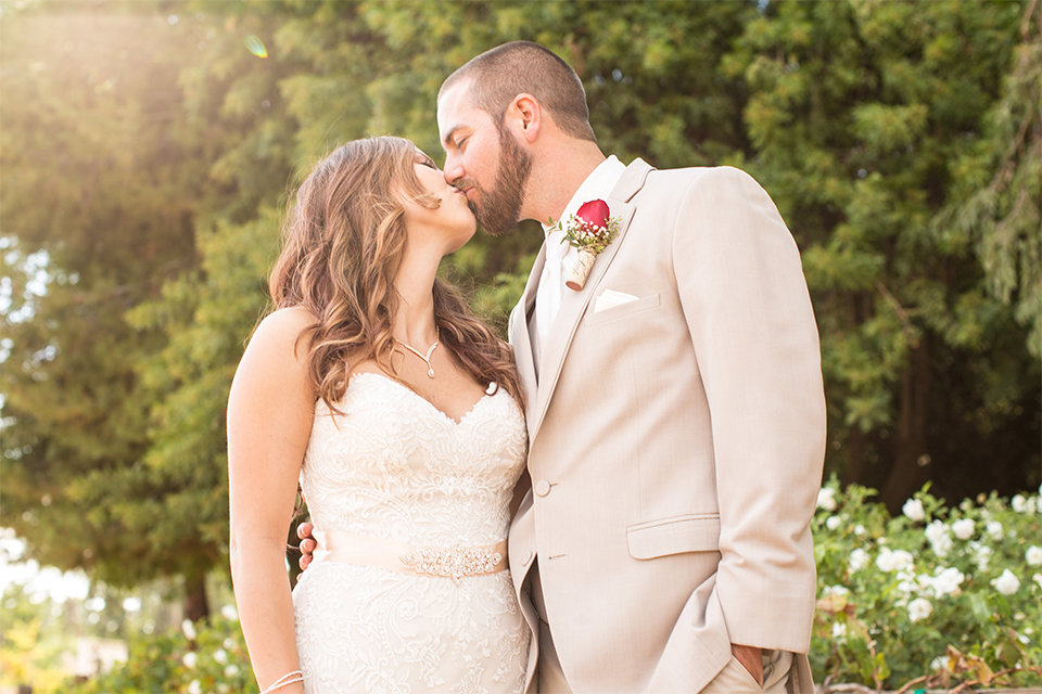 Temecula outdoor rustic wedding at lake oak meadows bride form fitting strapless gown with sweetheart neckline and lace detail with long veil and groom tan notch lapel suit with matching vest and white dress shirt and long white tie with red floral boutonniere standing and kissing