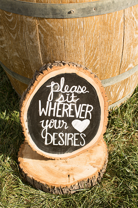 Temecula outdoor rustic wedding at the lake oak meadows ceremony decor wine barrel with wood tree stump and black and white chalkboard design on the grass wedding photo idea for ceremony decor