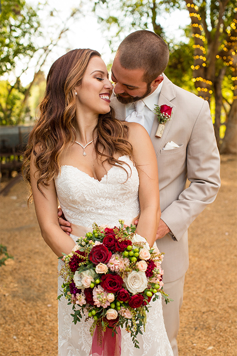 Temecula outdoor rustic wedding at lake oak meadows bride form fitting strapless gown with sweetheart neckline and lace detail with long veil and groom tan notch lapel suit with matching vest and white dress shirt and long white tie with red floral boutonniere hugging and bride holding white and red floral bridal bouquet with red ribbon decor