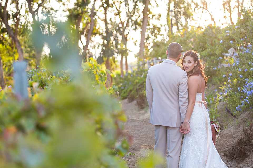 Temecula outdoor rustic wedding at lake oak meadows bride form fitting strapless gown with sweetheart neckline and lace detail with long veil and groom tan notch lapel suit with matching vest and white dress shirt and long white tie with red floral boutonniere holding hands and bride holding white and red floral bridal bouquet