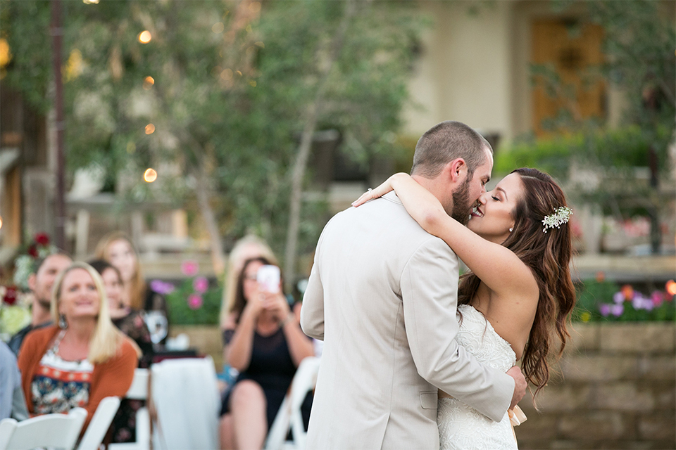 Temecula outdoor rustic wedding at lake oak meadows bride form fitting strapless gown with sweetheart neckline and lace detail with long veil and groom tan notch lapel suit with matching vest and white dress shirt and long white tie with red floral boutonniere dancing and kissing