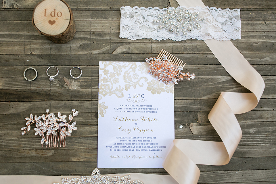 Temecula outdoor rustic wedding at lake oak meadows wedding invitations white invitations with small calligraphy writing with lace detail and light grey wood background and light pink floral decor and rustic wood elements