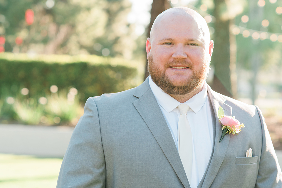 Orange county outdoor wedding at turnip rose garden groom heather grey notch lapel suit with matching vest and white dress shirt with long white tie and blush pink floral boutonniere
