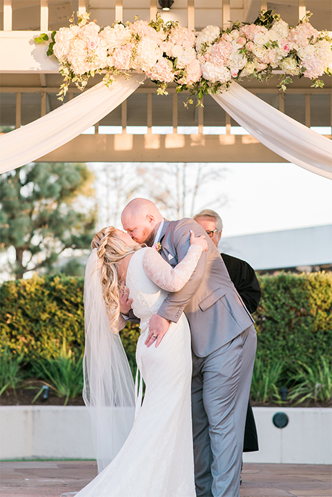Orange county outdoor wedding shoot at turnip rose garden bride form fitting gown with lace detail and long sleeves with long veil and sweetheart neckline with groom heather grey notch lapel suit with matching vest and white dress shirt with long white tie and blush pink floral boutonniere kissing during ceremony