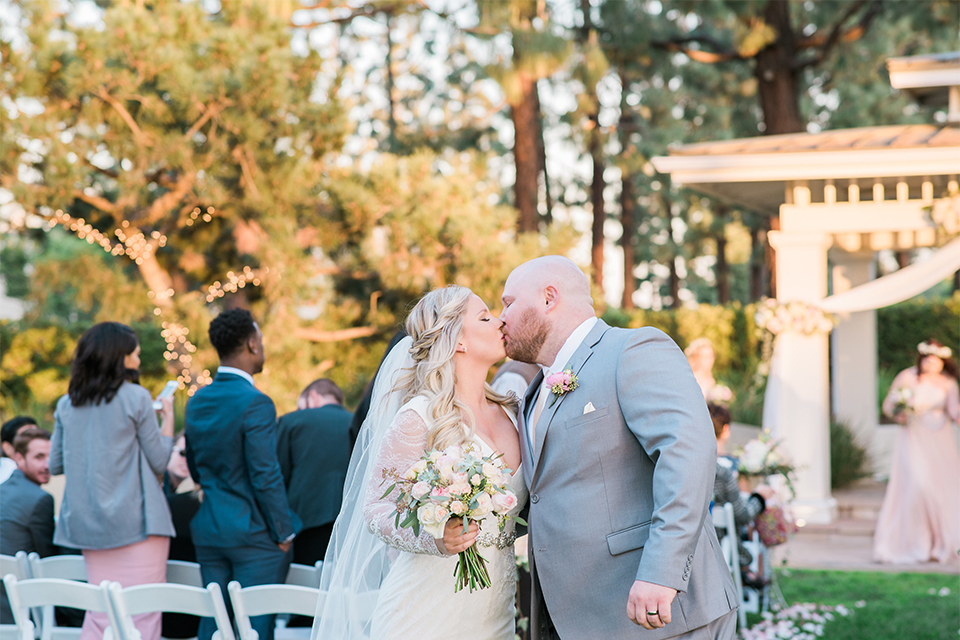 Orange county outdoor wedding shoot at turnip rose garden bride form fitting gown with lace detail and long sleeves with long veil and sweetheart neckline with groom heather grey notch lapel suit with matching vest and white dress shirt with long white tie and blush pink floral boutonniere kissing after ceremony