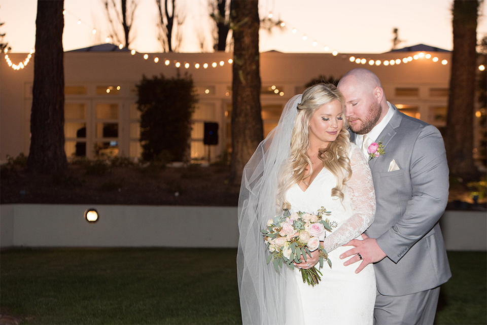 Orange county outdoor wedding shoot at turnip rose garden bride form fitting gown with lace detail and long sleeves with long veil and sweetheart neckline with groom heather grey notch lapel suit with matching vest and white dress shirt with long white tie and blush pink floral boutonniere hugging