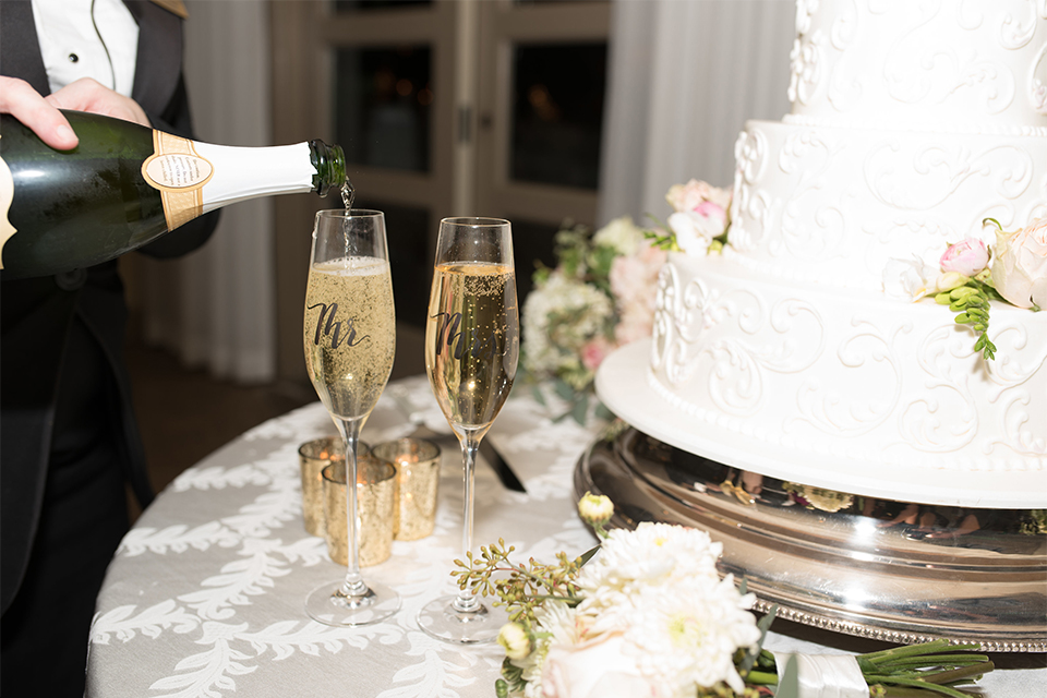 Orange county outdoor wedding at turnip rose garden wedding cake three tier white wedding cake with lace design and white and pink flowers on top and on side with silver cake stand and champagne glasses with white flowers and white linen decor