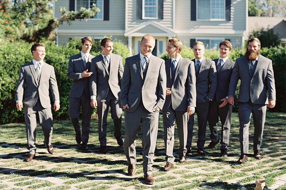 Southern california outdoor wedding at the riverview free church groom grey notch lapel suit with matching vest and white dress shirt with long grey tie and light blue floral boutonniere with groomsmen grey notch lapel suits with long light blue ties walking
