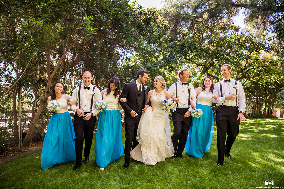 Vintage garden outdoor wedding at green gables estate bride form fitting lace gown with high lace neckline and groom black shawl lapel tuxedo with white dress shirt and long black skinny tie walking with wedding party bridesmaids white and blue dresses and groomsmen black tuxedos with light blue shirts and black bow ties and black suspenders walking