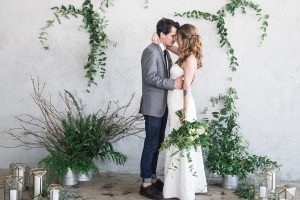 Los angeles minimal and classic wedding shoot at fd studio bride a line strapless gown with straight neckline and lace skirt with pockets and simple design with groom grey notch lapel suit with white dress shirt and long black skinny tie with a white floral boutonniere standing and hugging during ceremony bride holding green floral bridal bouquet