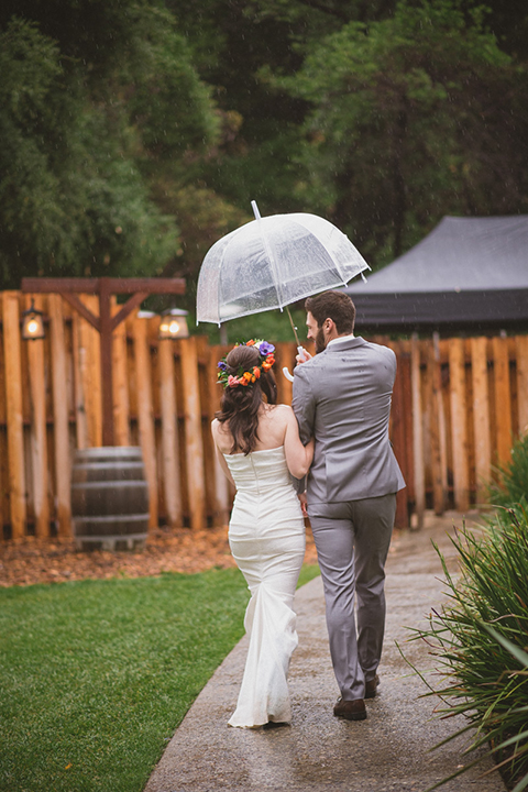 Temecula outdoor wedding at temecula creek inn bride form fitting simple strapless gown with a straight neckline and teal rain boots with groom grey notch lapel suit with a white dress shirt and long brown tie with an orange floral boutonniere holding hands and walking under clear umbrella