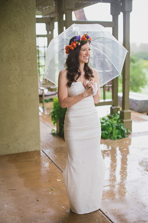 Temecula outdoor wedding at temecula creek inn bride form fitting simple strapless gown with a straight neckline and teal rain boots wearing colorful floral crown holding colorful floral bridal bouquet standing under clear umbrella