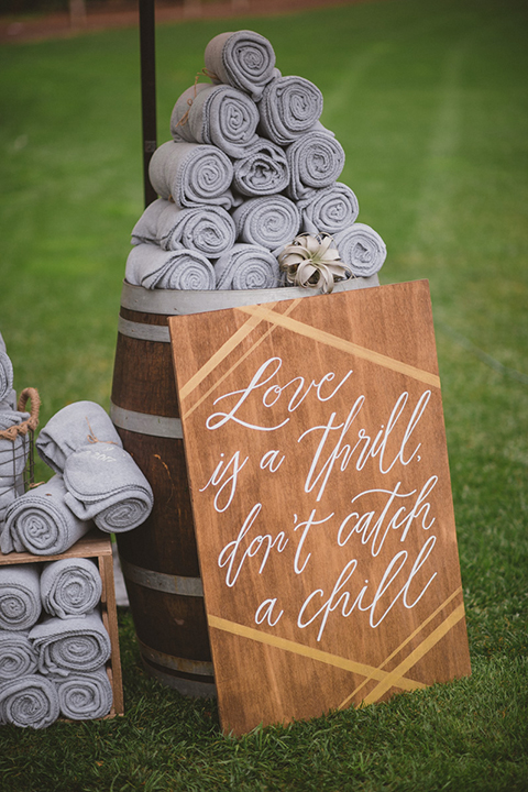 Temecula outdoor wedding at temecula creek inn ceremony set up with decor wooden sign with white calligraphy writing and towel for rain on wine barrel wedding photo idea for ceremony decor