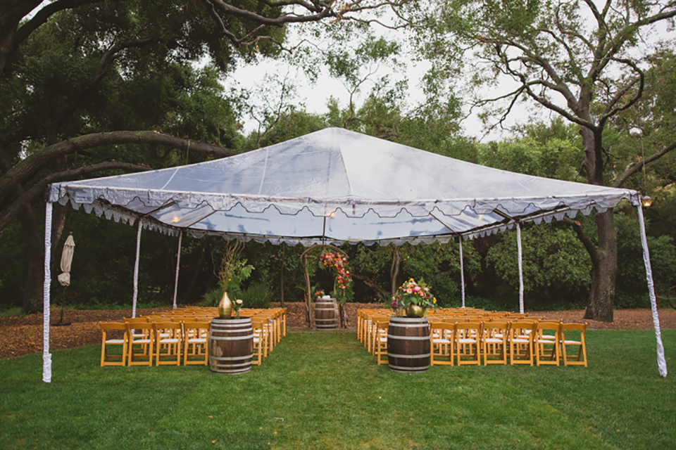 Temecula outdoor wedding at temecula creek inn ceremony set up with brown and white chairs with wine barrels and colorful flowers on top with clear tent covering the rain on grass wedding photo idea for ceremony set up