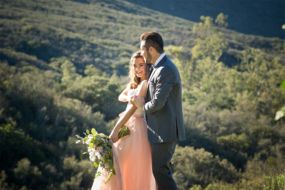San diego outdoor woodland wedding shoot bride blush pink chiffon strapless gown with a sweetheart neckline and groom navy blue shawl lapel tuxedo with a matching vest and white dress shirt with a long pink striped tie and white floral boutonniere holding hands and dancing