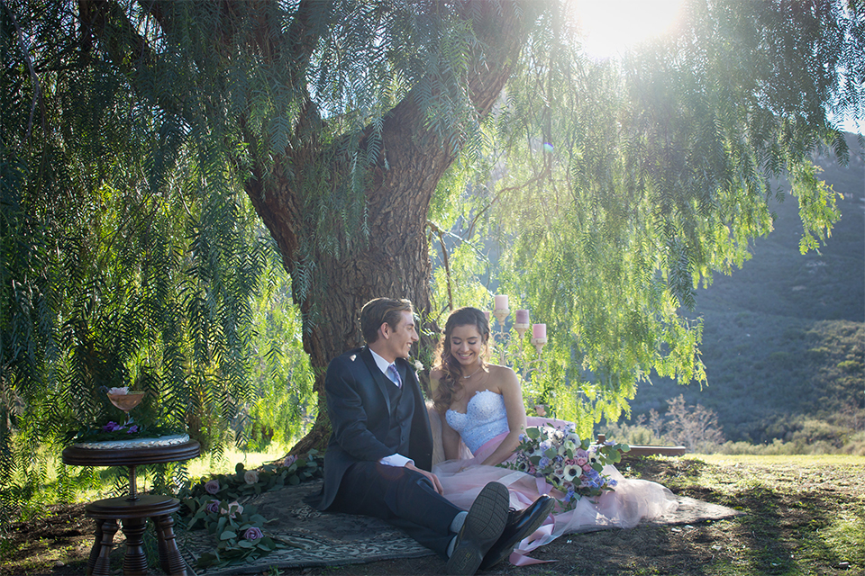 San diego outdoor woodland wedding shoot bride blush pink chiffon strapless gown with a sweetheart neckline and groom navy blue shawl lapel tuxedo with a matching vest and white dress shirt with a long pink striped tie and white floral boutonniere sitting on blanket under tree