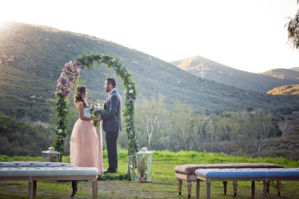 San diego outdoor woodland wedding shoot bride blush pink chiffon strapless gown with a sweetheart neckline and groom navy blue shawl lapel tuxedo with a matching vest and white dress shirt with a long pink striped tie and white floral boutonniere standing and holding hands during ceremony bride holding white floral bridal bouquet