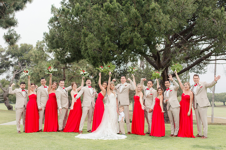 Los angeles wedding at los verdes golf club bride form fitting gown with lace detail and low back design with thin straps and long veil with groom tan notch lapel suit with matching vest and white dress shirt with matching tan bow tie and white pocket square with white and red floral boutonniere hugging with wedding party cheering bridesmaids long red dresses and groomsmen tan suits with bow ties
