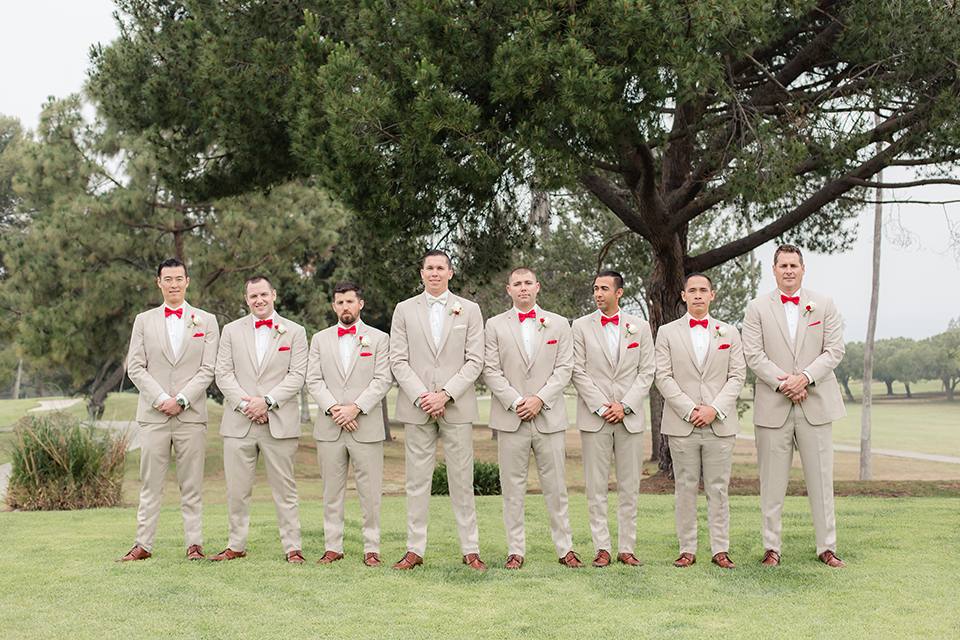 Los angeles wedding at los verdes golf club bride form fitting gown with lace detail and low back design with thin straps and long veil with groom tan notch lapel suit with matching vest and white dress shirt with matching tan bow tie and white pocket square with white and red floral boutonniere standing with groomsmen tan suits with bow ties