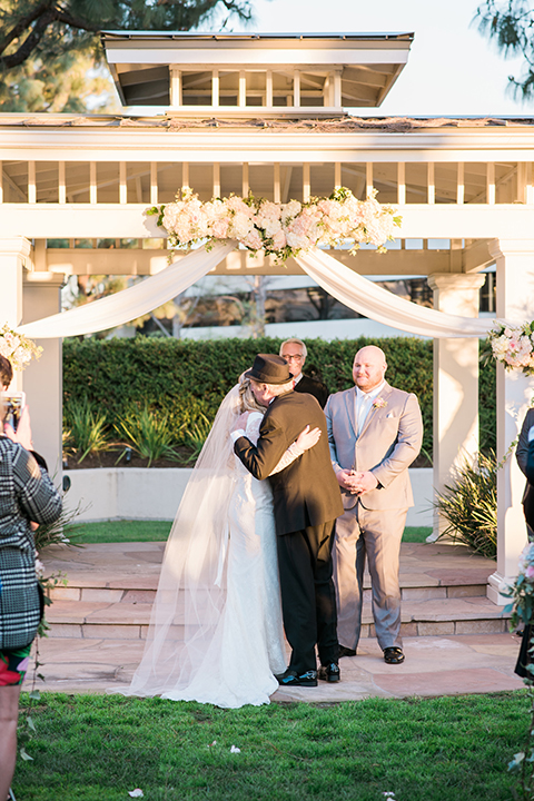 Orange county outdoor wedding shoot at turnip rose garden bride form fitting gown with lace detail and long sleeves with long veil and sweetheart neckline with groom heather grey notch lapel suit with matching vest and white dress shirt with long white tie and blush pink floral boutonniere bride walking down the aisle during ceremony hugging dad