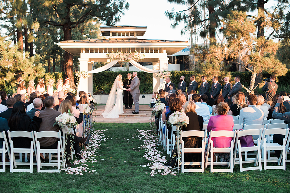 Orange county outdoor wedding shoot at turnip rose garden bride form fitting gown with lace detail and long sleeves with long veil and sweetheart neckline with groom heather grey notch lapel suit with matching vest and white dress shirt with long white tie and blush pink floral boutonniere holding hands during ceremony